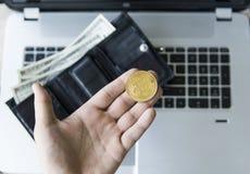 金黄bitcoin硬币在人有一台膝上型计算机的` s手上在有金钱的背景和皮革钱包 举行隐藏的人 免版税库存照片
