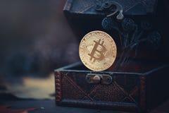 金黄Bitcoin 珍宝-神奇隐藏的货币 在黑暗的背景的老木箱真正金钱 温暖定调子 库存图片