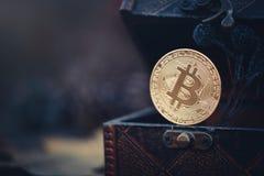 金黄Bitcoin 珍宝-神奇隐藏的货币 在黑暗的背景的老木箱真正金钱 温暖定调子 库存照片
