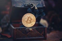 金黄Bitcoin 珍宝-神奇隐藏的货币 在黑暗的背景的老木箱真正金钱 温暖定调子 免版税库存照片