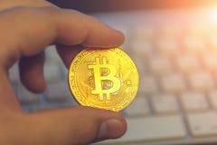 金黄cryptocurrency bitcoin在键盘背景的人手上 免版税库存图片