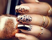 金黄与宝石和闪闪发光的假日样式明亮的修指甲 免版税库存图片