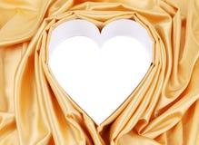 金黄丝绸的白色心脏 库存照片
