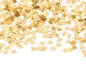 从金黄五彩纸屑的背景在星形状 库存图片