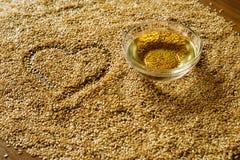 金黄亚麻籽和一个碗油 免版税库存图片
