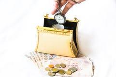 金黄传动器、金钱和怀表、时间和财政concep 免版税库存照片