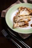 金黄俄国薄煎饼有奶油色板材特写镜头黑暗背景 库存图片