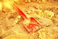 金黄光亮的沙子和塑料sovochke 金矿的标志 库存照片