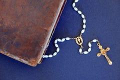 金黄十字架和古老圣经反对蓝色背景 库存照片