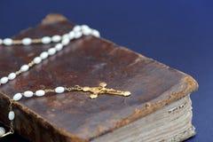 金黄十字架和古老圣经反对蓝色背景 图库摄影