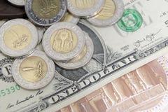金黄和变成银色在一张美国美元钞票的1种埃及磅金属硬币 免版税库存照片