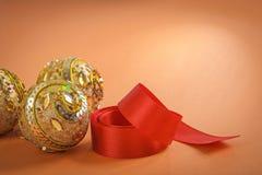 金黄圣诞节中看不中用的物品和红色丝带在棕色背景 免版税库存照片