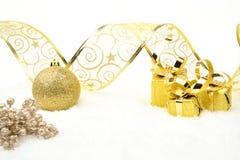 金黄圣诞节礼物、中看不中用的物品丝带和花揪在雪 免版税库存照片