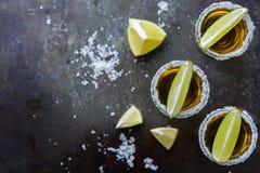 金黄墨西哥龙舌兰酒射击了与绿色石灰和盐 免版税库存图片
