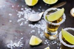 金黄墨西哥龙舌兰酒射击了与绿色石灰和盐 免版税库存照片