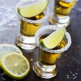 金黄墨西哥龙舌兰酒射击了与绿色石灰和盐 库存图片