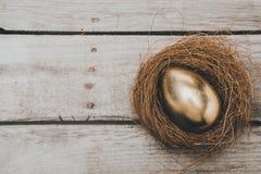 金黄复活节彩蛋特写镜头顶视图在巢的在木桌上 库存照片
