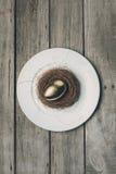 金黄复活节彩蛋顶视图在巢的在木桌上的白色板材 免版税库存照片