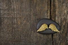 金黄天使飞过与在老木背景的黑石头为 免版税库存照片