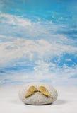 金黄天使飞过与在蓝色天堂背景的石头spir的 免版税库存图片