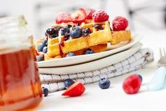 金黄奶蛋烘饼用莓果和一个瓶子蜂蜜 免版税库存图片