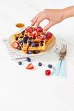 金黄奶蛋烘饼用莓果和杯子蜂蜜 免版税库存照片
