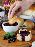 金黄小圆面包和莓果和花围拢的莓果果酱 库存照片