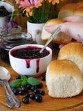 金黄小圆面包和莓果果酱 女性手采取小圆面包 免版税库存照片