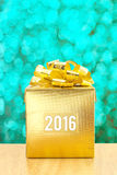 金黄当前箱子与在绿色bokeh光后面的2016个词年 库存照片