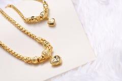 金黄心脏垂饰,脖子鞋带,金黄镯子 免版税库存图片