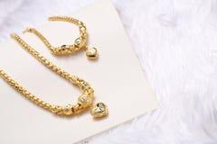 金黄心脏垂饰,脖子鞋带,金黄镯子 库存照片