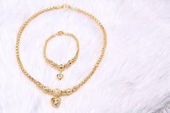 金黄心脏垂饰,脖子鞋带,金黄镯子 库存图片
