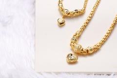 金黄心脏垂饰,脖子鞋带,金黄镯子 免版税图库摄影