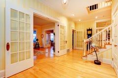 金黄明亮的黄色豪华家庭主要走廊,与楼梯的入口。 免版税库存照片