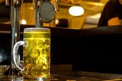 金黄桶装啤酒发光的大啤酒杯  免版税库存照片
