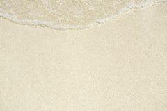 金黄沙子和透明水,纹理 库存图片
