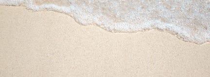 金黄沙子和透明水,纹理 免版税库存照片