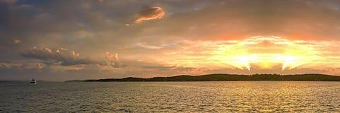 金黄海洋海岛日落通过云彩和与水反射和小船 免版税库存照片