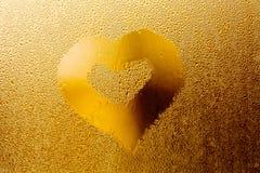 金黄爱心脏为情人节 在透明玻璃背景,橙色颜色摘要的水滴样式 免版税库存照片