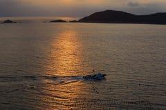 金黄的小船过去风平浪静在日落 免版税库存照片
