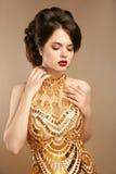 金黄礼服的典雅的夫人在米黄背景 库存图片