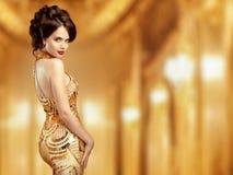 金黄礼服的典雅的夫人在米黄背景 免版税库存图片