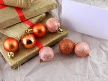 金黄礼物盒设置了与红色丝带、圣诞节球和空的卡片 图库摄影
