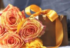 金黄礼物组装、桔子玫瑰色花和黄色装饰丝带 免版税图库摄影