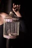 金黄笼子在黑暗的背景的女性手上 自由和奴役的标志在婚姻 免版税库存照片