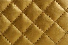金黄缝制的皮革背景 免版税库存照片