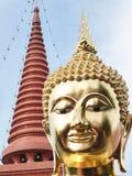 金黄菩萨雕象棕色马赛克头和上面完成了塔有蓝天背景 库存图片