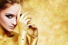 金黄闪烁背景的美丽的妇女 库存照片