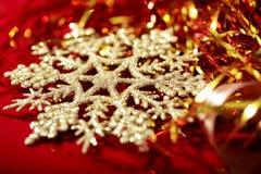 金黄雪花和闪亮金属片圣诞节背景 免版税库存图片