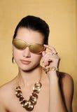 金黄首饰的美丽的妇女 免版税库存照片